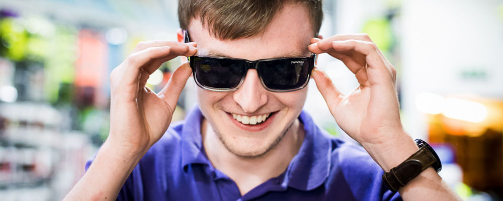 Man putting on sunglasses in a shop